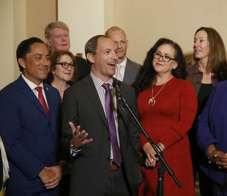 Assemblyman Brian Maienschein, center, discusses his decision to switch party registration from Republican to Democrat at a news conference, Thursday, Jan. 24, 2019, in Sacramento, Calif. Maienschein was flanked by Democratic Assembly members, from left, including Todd Gloria of San Diego, Eloise Gomez Reyes, of San Bernardino, Mark Stone of Scotts Valley, Kevin McCarty of Sacramento, Lorena Gonzalez Fletcher of San Diego and Jacqui Irwin, of Thousand Oaks. (AP Photo/Rich Pedroncelli)