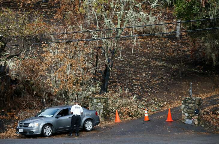 A security guard blocks the entrance to a home on Bennett Lane in Calistoga, Calif. on Friday, Nov. 10, 2017 where investigators believe is the origin of the Tubbs Fire. PG&E filed legal papers suggesting that third party electrical equipment, not theirs, may have been the cause of last month's deadly Tubbs Fire.