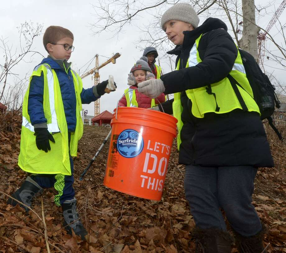 Westport resident Emma Cusato and her children, Jimmy, 8, and Anna, 5, pick up trash as Surfrider and SkipThePlasticNorwalk.org organize a clean-up of Oyster Shell Park in support of Norwalk's plastic bag ban on Jan. 19 in Norwalk. Photo: Erik Trautmann / Hearst Connecticut Media / Norwalk Hour
