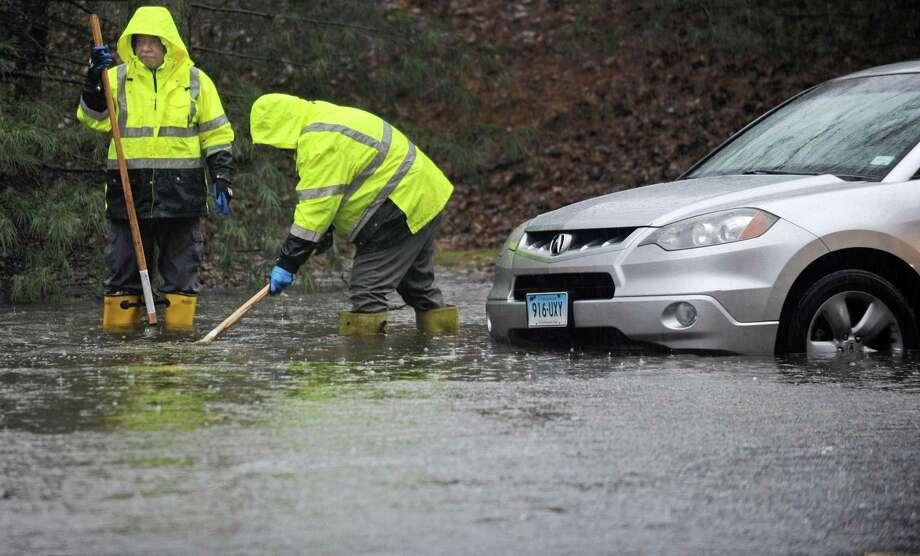 Norwalk DPW employees clear storm drains on Glover Ave. during the rainstorm Thursday, January 24, 2018, in Norwalk, Conn. Photo: Erik Trautmann / Hearst Connecticut Media / Norwalk Hour