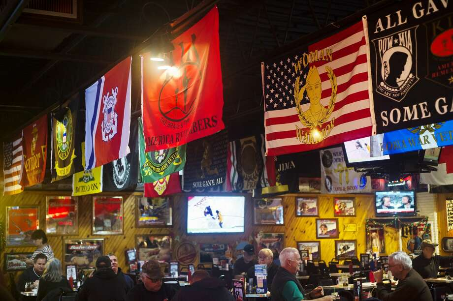 Various flags for veterans organizations and branches of the armed forces hang from the ceiling inside Boulevard Lounge at 316 S. Saginaw Road in Midland. (Katy Kildee/kkildee@mdn.net) Photo: (Katy Kildee/kkildee@mdn.net)