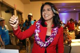 FILE - In this Nov. 6, 2018, file photo, Rep. Tulsi Gabbard, D-Hawaii, greets supporters in Honolulu. Gabbard is formally launching her campaign for president. The 37-year-old on Thursday, Jan. 24, 2019, announced she would seek the nation's highest office with a video posted on her website. (AP Photo/Marco Garcia, File)