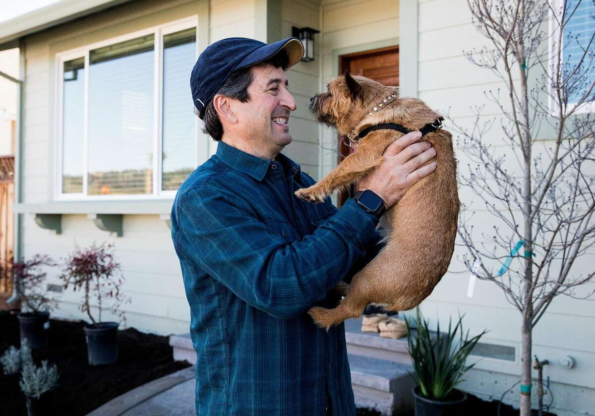 Joe Albano holds his dog, Pipsy, in front of his newly-constructed home that was previously destroyed during the Tubbs Fire in the Coffey Park neighborhood of Santa Rosa, Calif. Thursday, Jan. 24, 2019.