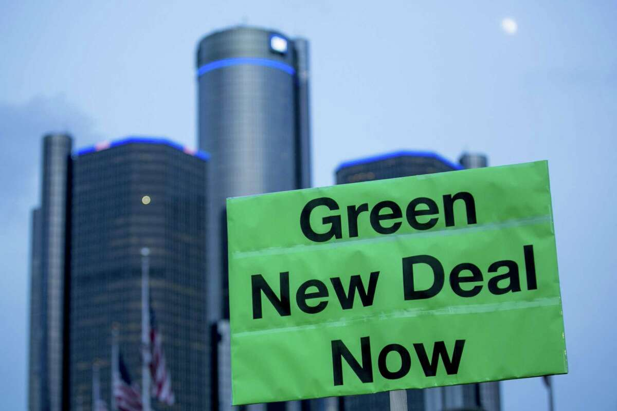 """A demonstrator holds a sign that reads """"Green New Deal Now"""" at a United Auto Workers (UAW) candlelight vigil for General Motors Co. workers at assembly plants targeted to close at Hart Plaza in Detroit, Michigan, U.S., on Friday, Jan. 18, 2019. General Motors Co.'s decision to close five North American factories by the end of 2019 puts more than 6,700 salaried and hourly jobs at risk, unless GM and its unions find some new products for them to build. Photographer: Anthony Lanzilote/Bloomberg"""