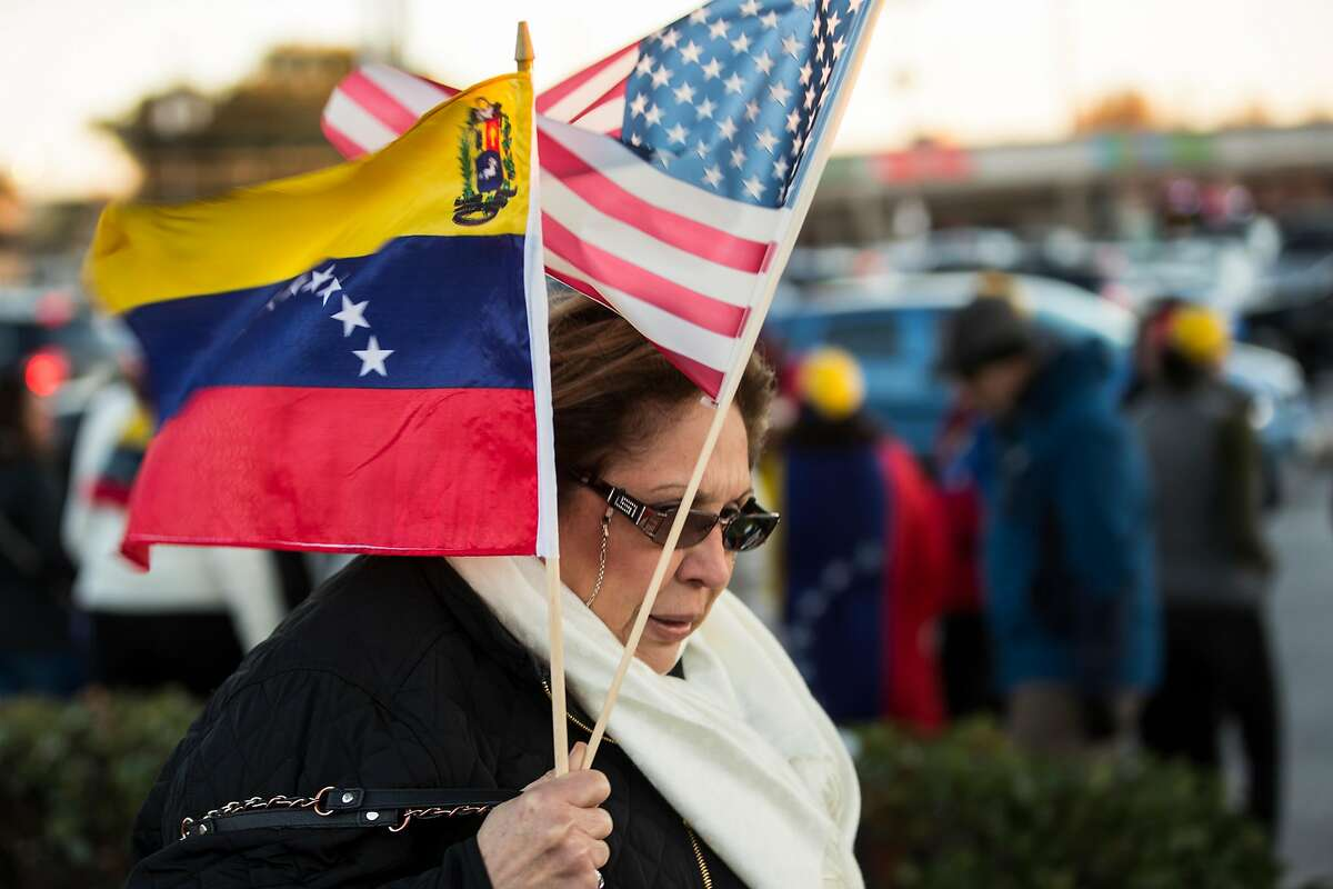 Carmen Nino carries a Venezuelan flag and an American flas she she joins local Venezuelans to demonstrate in reaction to recent political happenings in their home country on Wednesday, Jan. 23, 2019, in Houston. The demonstrators are gathering in support of Opposition leader Juan Guaido, who swore himself in as President of Venezuela, and against President Nicol�s Maduro. President Trump announced today that he is recognizing Venezuelan opposition leader.