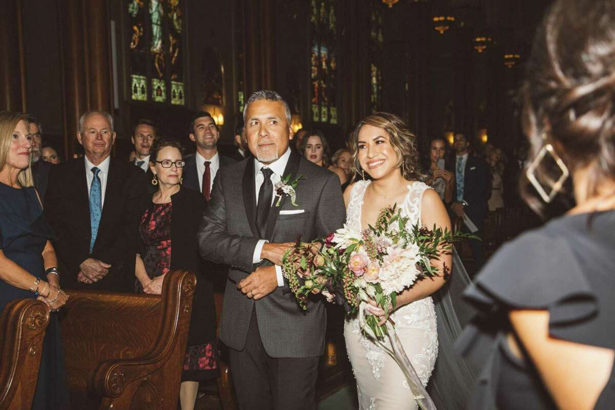 Mariano Castro escorts his daughter Christina down the aisle at St. Paul's Catholic Church. Aug. 11, 2018