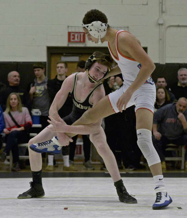 Trumbull's Jack Ryan, in black, and Danbury's Tyler Johnson, in white, wrestle in the 120-pound weight class on Jan. 16 at Trumbull High School. Photo: H John Voorhees III / Hearst Connecticut Media / The News-Times