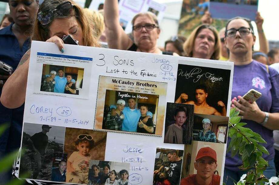 Jeanmarie McCauley, left, of Rockland, Mass., rests her head on a sign she made of her three children who died within three years to drug addiction, as family and friends who lost loved ones to OxyContin and opioid overdoses stage a protest outside the headquarters of Purdue Pharma in Stamford on Friday, Aug. 17, 2018. Photo: AP Photo /Jessica Hill