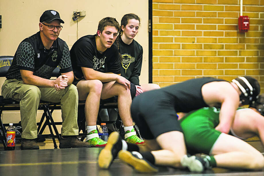 Bullock Creek twins Tyler Kutzke (center) and Sydney Kutzke (right) watch a teammate wrestle during Wednesday match against Freeland at the Lancers' gym. Photo: Katykildee/kildee@mdn.net