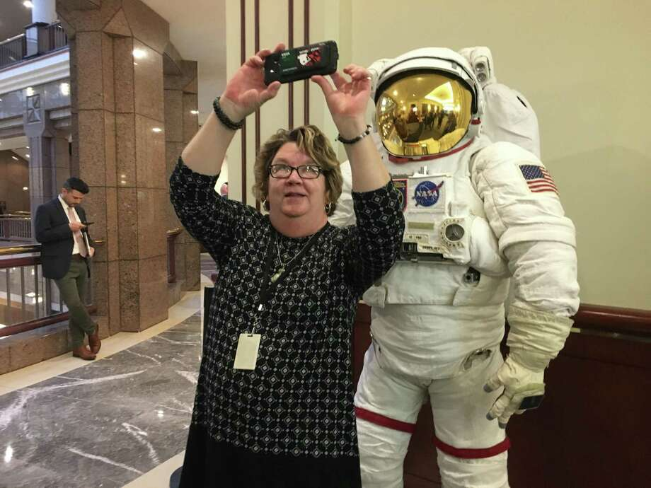 Terri Reid, assistant clerk at the General Assembly's insurance committee, takes a selfie with the space suit at the legislative office building in Hartford Thursday, Jan. 24, 2019, for the announcement of an international space summit in Hartford in May. Photo: Dan Haar /Hearst Connecticut Media