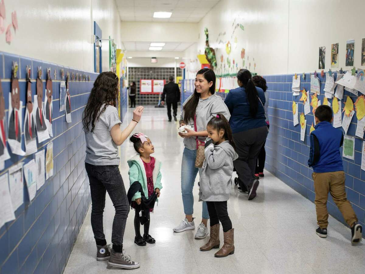 Krystal Olivarez and her daughters Krista Olivarez, 4, left, and Kaylee Olivarez, 6, at right, talk with Krista's Pre-K teacher Keleigh Perry, left, during an event last month at Gardendale Elementary School introducing parents and their children to the proposed partnership between the Edgewood ISD school and Pre-K 4 SA.