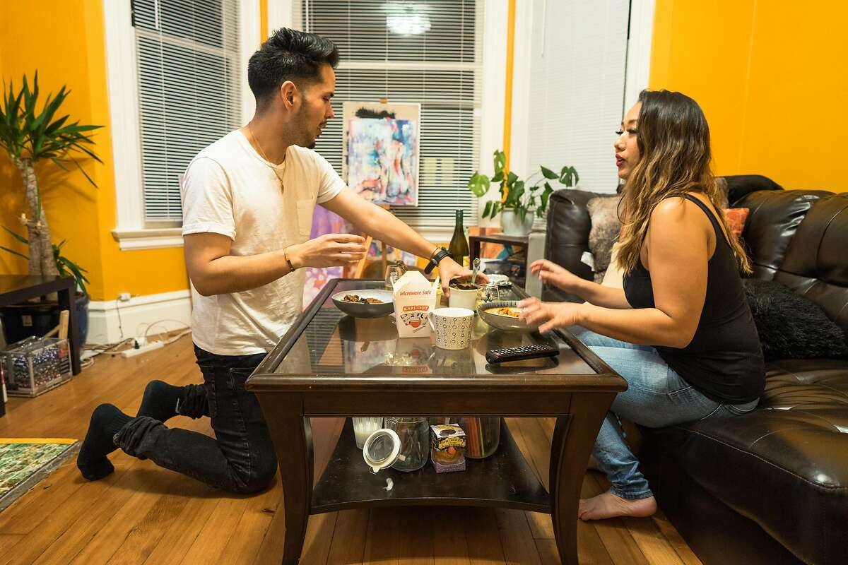 Stephen Torres-Esquer and his roommate Emerald Law split dinner before watching television at their apartment in San Francisco, Calif. on Thursday, Jan. 24, 2018. The city is trying to decide whether to spend $184 million dollars in windfall money on the homeless or teachers. Teachers like Torres-Esquer is barely making ends meet in the city and may return home to Stockton.