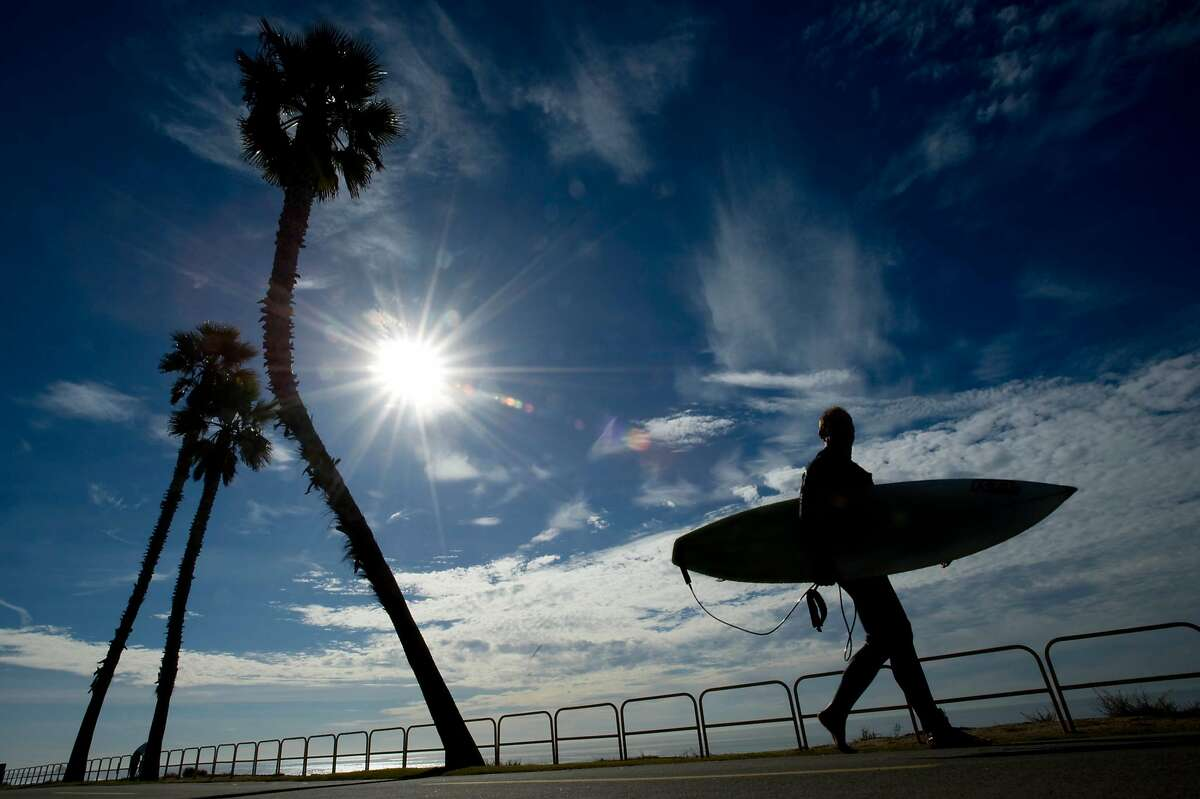 Steve Farnsworth, heads back to his car after a morning of surf near Dog Beach in Huntington Beach, Calif., Tuesday, Dec. 17, 2013. Temperatures at the beach hit a high of 82 degrees. (AP Photo/The Orange County Register, Joshua Sudock) MAGS OUT; LOS ANGELES TIMES OUT