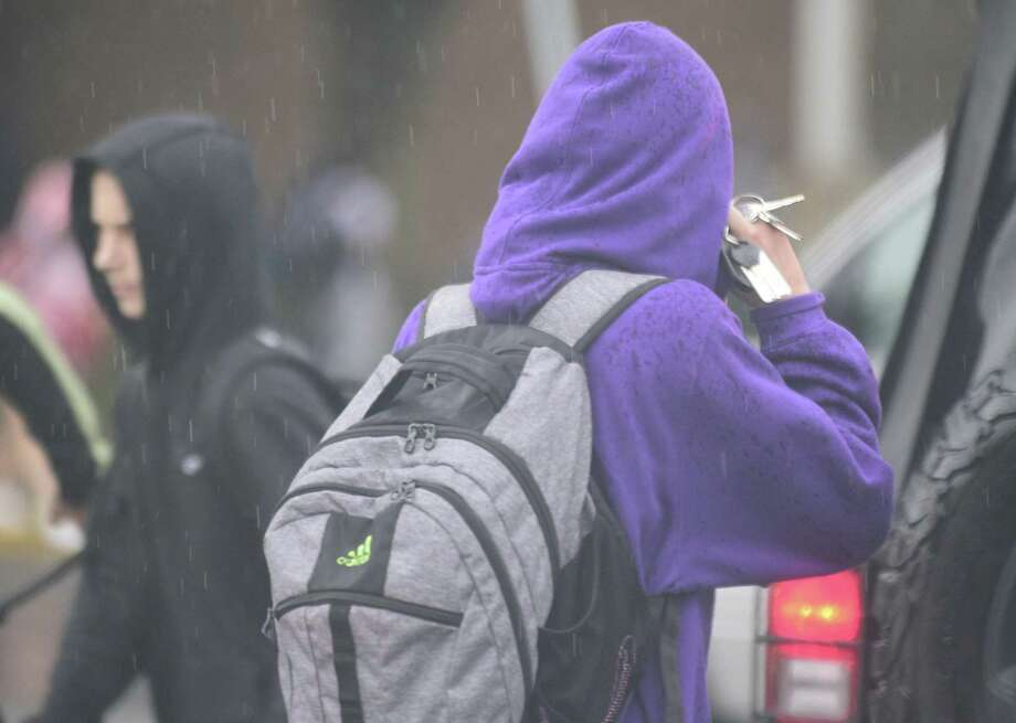 A Westhill student talks on a cellphone as school is dismissed. Photo: Matthew Brown / Hearst Connecticut Media / Stamford Advocate