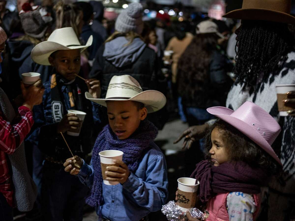 From left, siblings Miracle Irvin, 11, John Irvin, 9, Christian Irvin, 8, and Kimberley Irvin, 6, hold onto their warm cups of coffee along with their mother Johnny Ivin-Wilcher, right, during the 41st annual San Antonio Cowboy Breakfast held outside Cowboys Dancehall in San Antonio, Texas on Friday, January 25, 2019. The Cowboy Breakfast started in 1979 and has continued until this year where it draws over 30,000 people for free tacos, coffee and other food to kick off the San Antonio Stock Show and Rodeo.