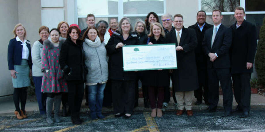 Edwardsville Community Foundation officials, right, present Main Street Community Center employees, left, with a check for $4,528 Thursday. Photo: Charles Bolinger | The Intelligencer