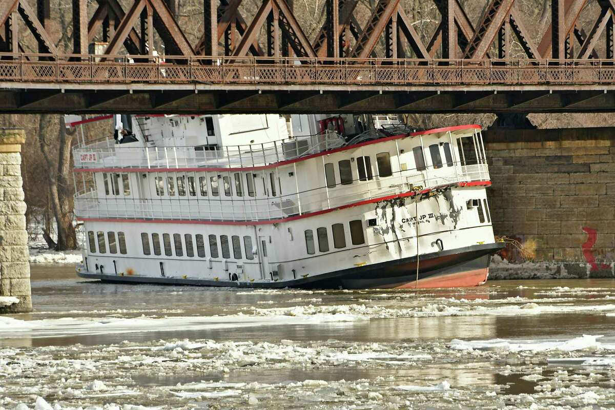 The Captain JP lll boat is seen stuck under the railroad bridge near the Corning Preserve on the Hudson River on Friday, Jan. 25, 2019 in Albany, N.Y. The boat, along with other barges including the Rusty Anchor, broke from the dock in Troy from the fast moving ice on the Hudson River. (Lori Van Buren/Times Union)