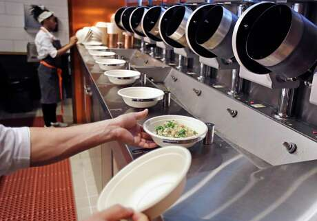 A worker lifts a lunch bowl off the production line at Spyce, a restaurant which uses a robotic cooking process, in Boston. Robots aren't replacing everyone, but a quarter of U.S. jobs will be severely disrupted as artificial intelligence accelerates the automation of today's work, according to a Brookings Institution report.