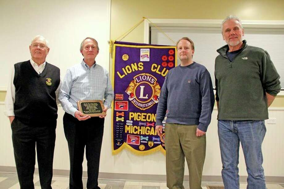 Fred Orr and his son, Bob, were presented with a plaque by the Pigeon Lions Club, celebrating 100 years of Orr's Drug Store being in Pigeon. Pictured are, from left, Lions member Crawford Kennedy, Fred Orr, Bob Orr, and Lions Club President Larry Leipprandt. (Mike Gallagher/Huron Daily Tribune)