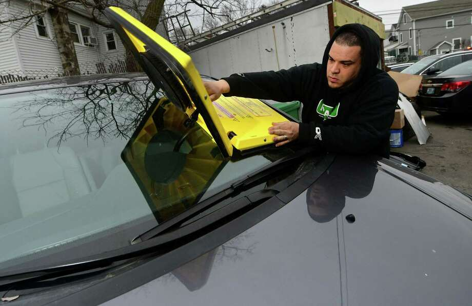 Fedor Auto Body tow truck driver and repossessor, Carlos Cabrera, demonstrates the Barnacle parking enforcement system Wednesday, January 23, 2019, at Fedor's garage in Norwalk, Conn. The device is affixed to the violators windshield with electronic suction cups and is removed with a release code and then returned in nearby bins. Fedor's is the biggest private property tower in the city and is rolling out the new tool aimed at making it cheaper for people caught parking illegally in private parking lots. Photo: Erik Trautmann / Hearst Connecticut Media / Norwalk Hour