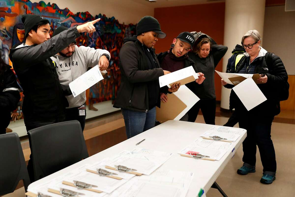 Volunteers coordinate their plans after receiving their maps at the SF Main Library for 2019 Homeless Point-In-Time Count in San Francisco, Calif., on Thursday, January 24, 2019.