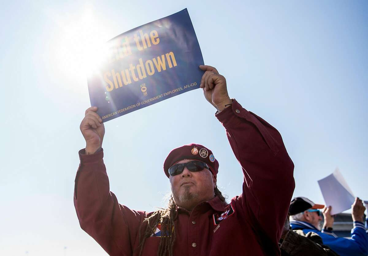Joe Kue Angeles carries a sign while joining furloughed federal workers and supporters during a rally and march at the Oakland International Airport in Oakland, Calif. Friday, Jan. 25, 2019 after the government shutdown has forced federal workers to miss their second paycheck.