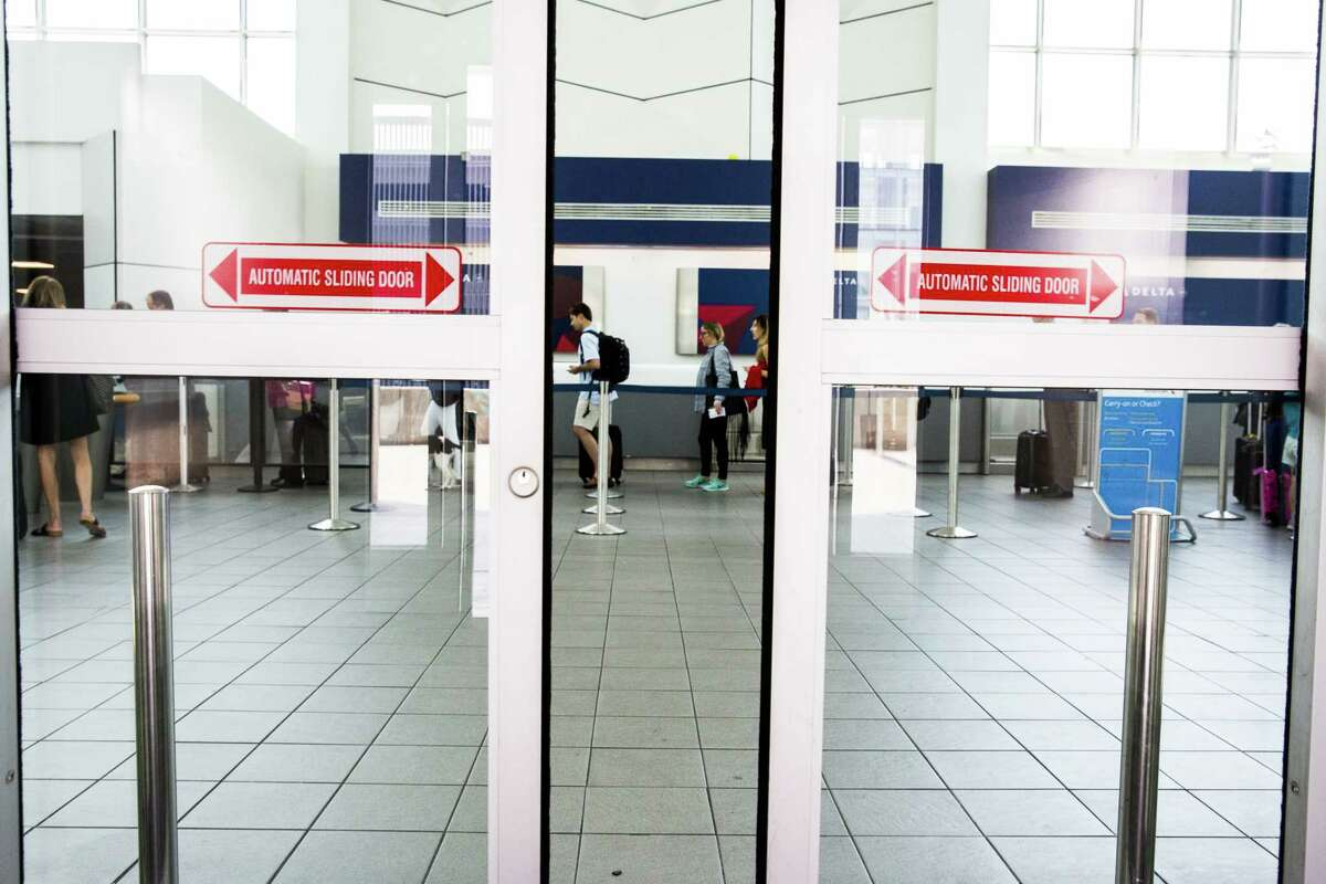 A sliding door closes as travelers stand in a security line at LaGuardia Airport in New York, U.S., on June 29, 2017.
