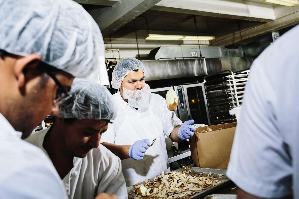 Jose Garcia, center, tosses a half-peeled potato at the Munchery kitchen in San Francisco, Calif. on Tuesday, April 19, 2016.