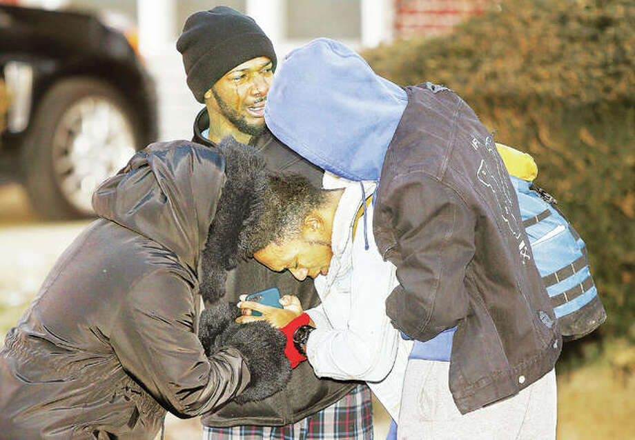 An Alton High School student, center, appears to pray with family members Friday morning after returning to his house in the 1300 block of Taylor Avenue in Alton where firefighters searched for him and distraught family members worried he was still inside the burning home. Heavy smoke was pouring from the small house in the early morning fire when firefighters arrived and were told a male and female were still inside. The woman escaped the house through a window before firefighters arrived and eventually told them she thought her son was still inside. Five Alton Police officers worked to keep distraught family members back before it was eventually discovered the teenager had left the house early for school. The house suffered extensive damage in the fire. Photo: John Badman | The Telegraph
