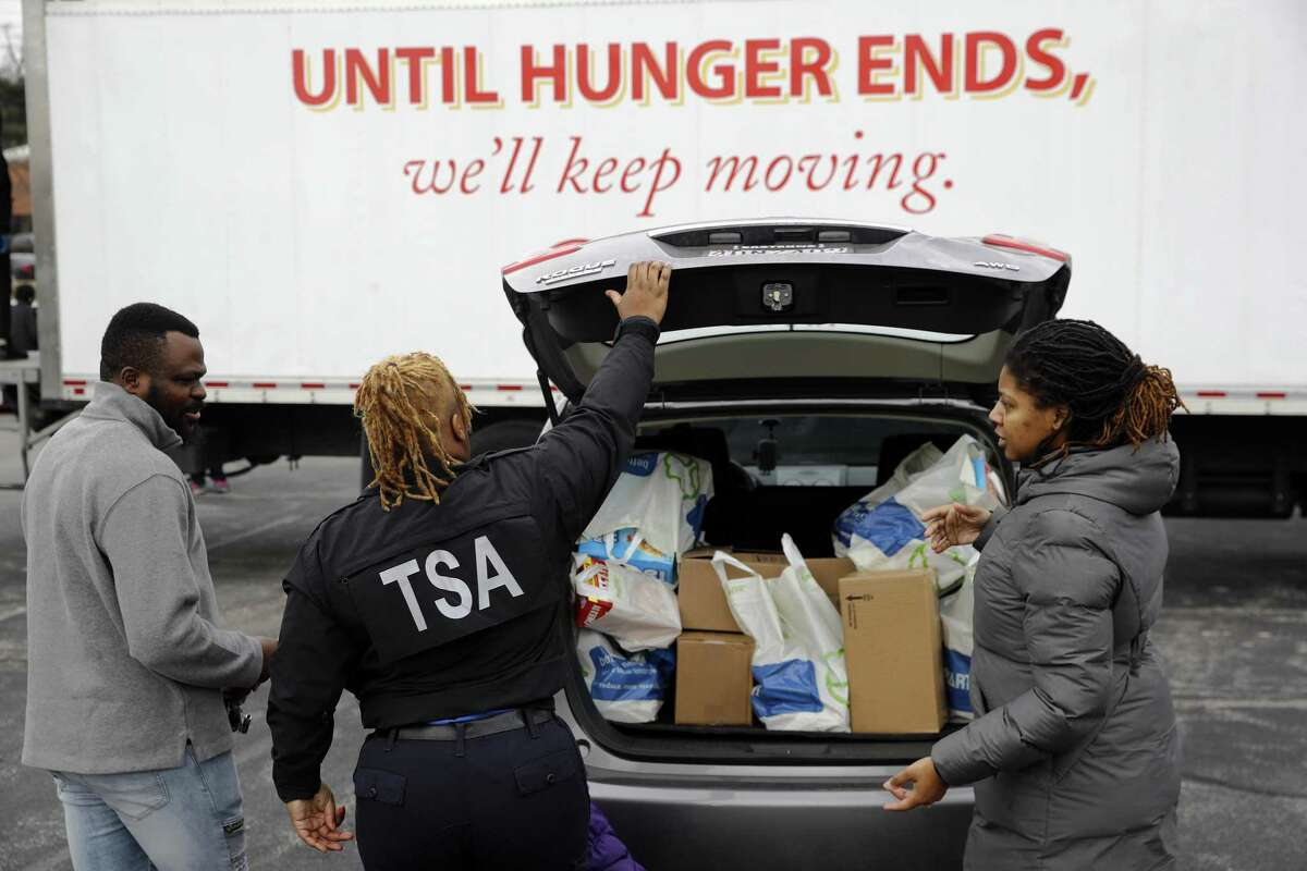 TSA employee Princess Young, center, loads food into a car after visiting a food pantry for furloughed government workers affected by the federal shutdown Wednesday in Baltimore.