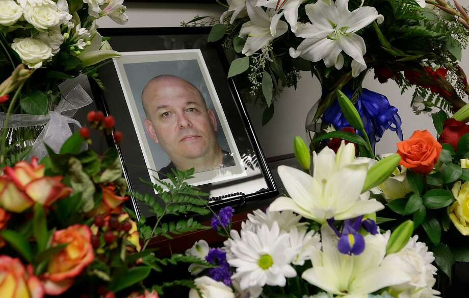 Flowers surround the photo of slain Sacramento County Deputy Sheriff Daniel Oliver,at the Sacramento County Sheriff's office in Sacramento, Calif. Oct, 28, 2014. Luis Enrique Monroy-Bracamonte, an undocumented immigrant, was charged in his slaying — a fact used by President Trump to feed anti-immigrant, pro-wall fervor. Photo: Rich Pedroncelli /AP / AP