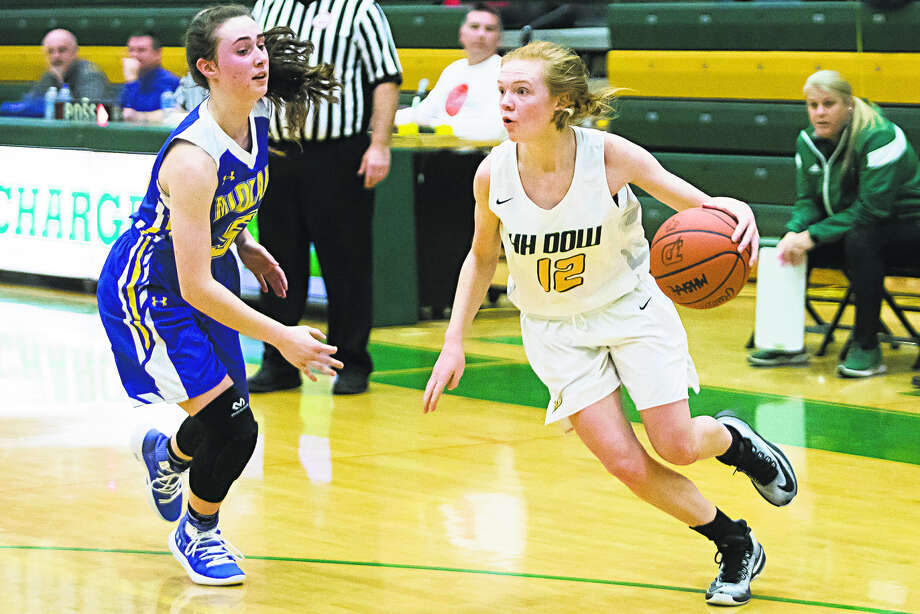 Dow High's Alexa Kolnitys tries to drive past Midland High's Olivia Carpenter during Friday's game at the Chargers' gym. Photo: Katykildee/kildee@mdn.net