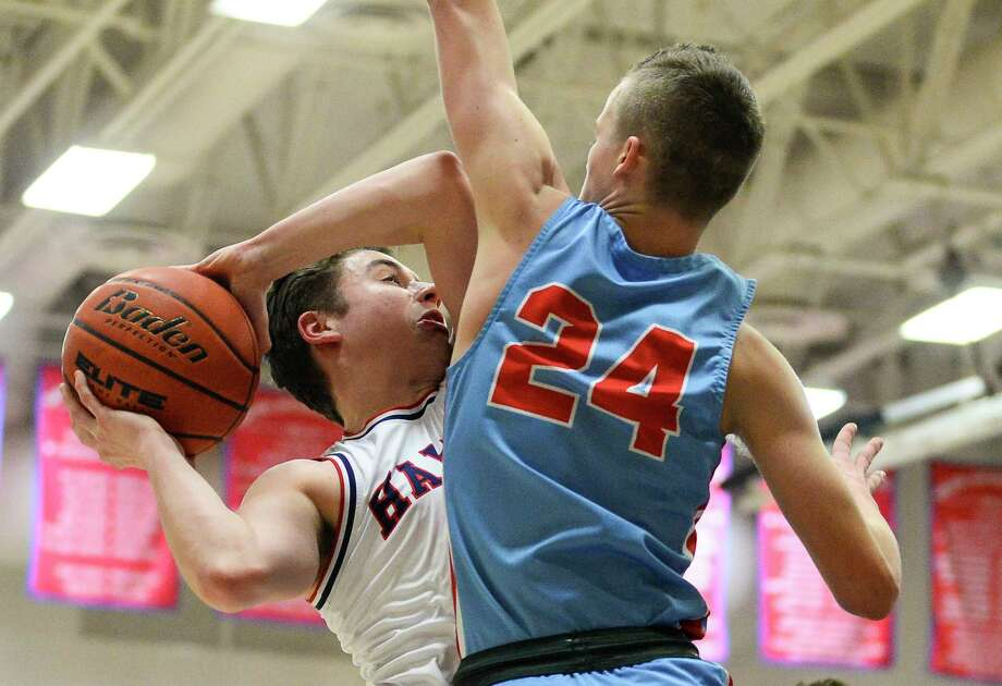 Hardin-Jefferson's Jaystan Davis attempts a layup as Lumberton's Brock Mcclure defends during the first half of the game in Hardin-Jefferson on Friday.