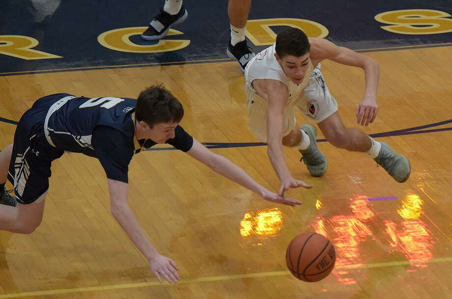 GFA boys basketball player David Basich, right, hits the floor to come up with a loose ball during a road game at Rye Country Day last week. Photo: Contributed Photo / Greenwich Time Contributed