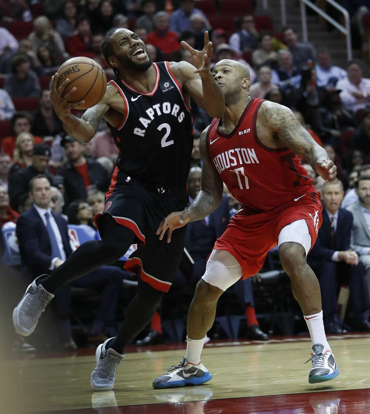 Toronto Raptors forward Kawhi Leonard (2) tries to beat out Houston Rockets forward PJ Tucker (17) during the second half of an NBA basketball game at Toyota Center, Friday, Jan. 25, 2019, in Houston.