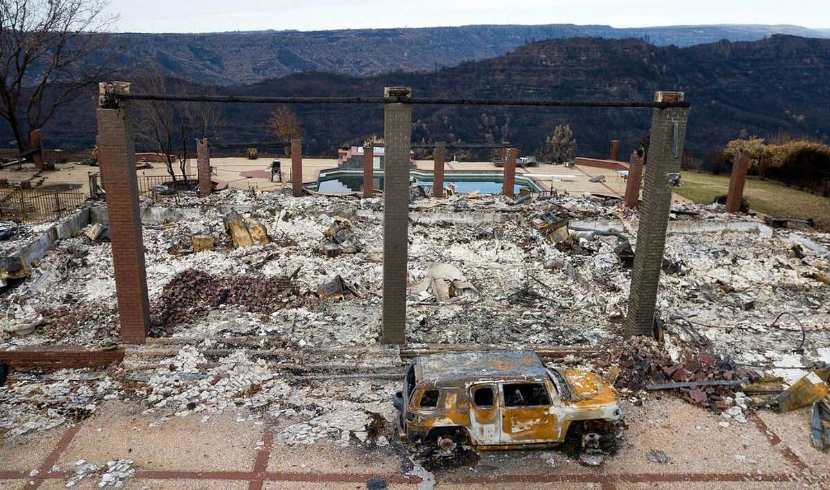 In this Dec. 3, 2018 file photo, a vehicle rests in front of a home leveled by the Camp Fire in Paradise, Calif.