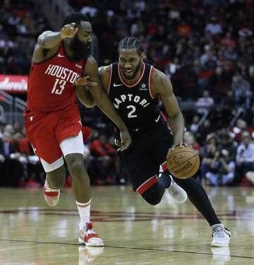 2d9489da61ea 3of3Toronto Raptors forward Kawhi Leonard (2) tries to work around Houston Rockets  guard James Harden (13) during the second half of an NBA basketball game ...