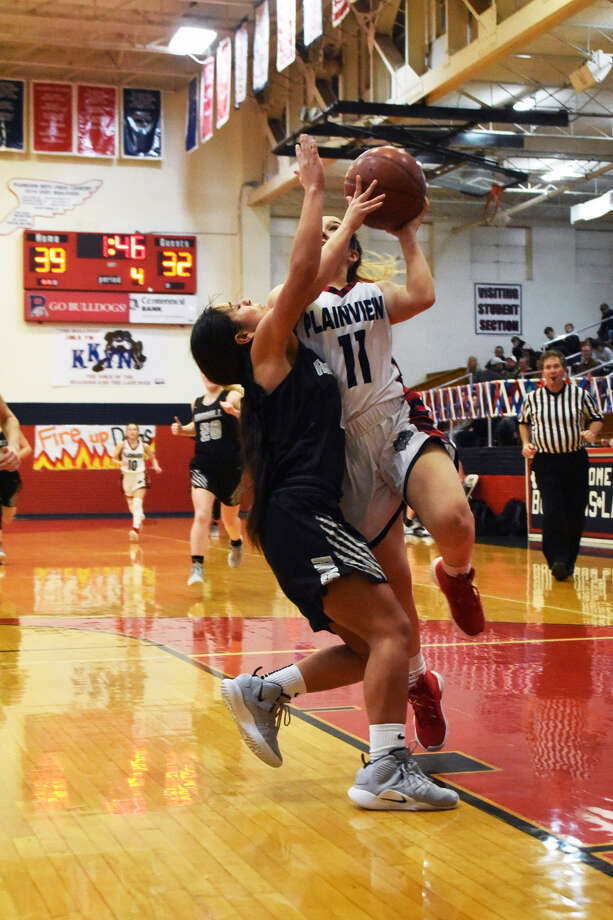 Plainview Lady Bulldogs sophomore guard Emily Sigala (11) draws a foul on Randall Lady Raiders Kamry Perez while going up for a shot during Friday night's District 3-5A girls basketball contest in Plainview. Photo: Claudia Lusk/Plainview Herald