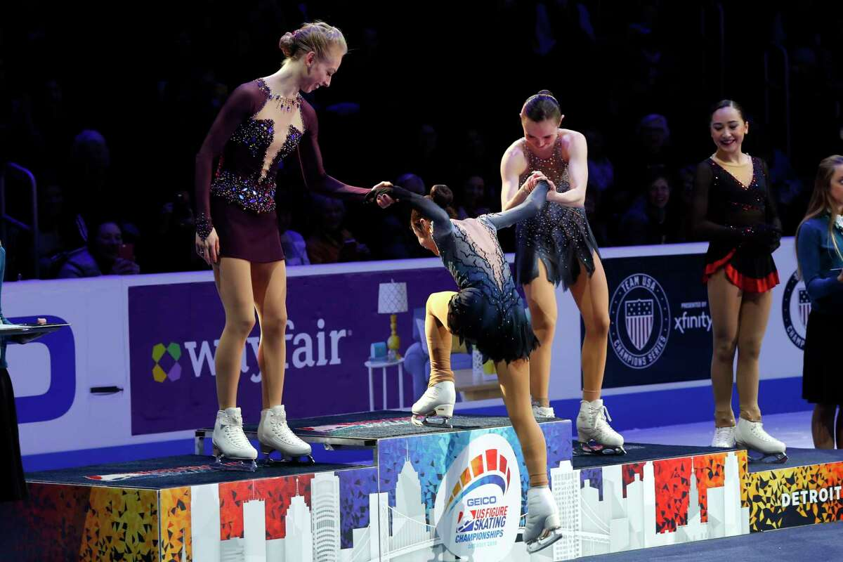 Women's champion Alysa Liu is helped onto the podium by Bradie Tennell, left, who finished in second, and Mariah Bell, who finished third, at the the U.S. Figure Skating Championships, Friday, Jan. 25, 2019, in Detroit.