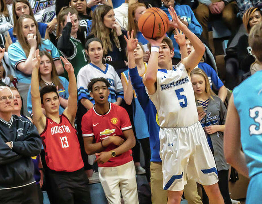 Marquette's Chris Hartrich (5) puts up a shot as the Marquette Catholic High student section cheers him on during Friday night's home victory over Jersey. At far right is Jersey's Alex Strebel. Photo: Nathan Woodside | The Telegraph