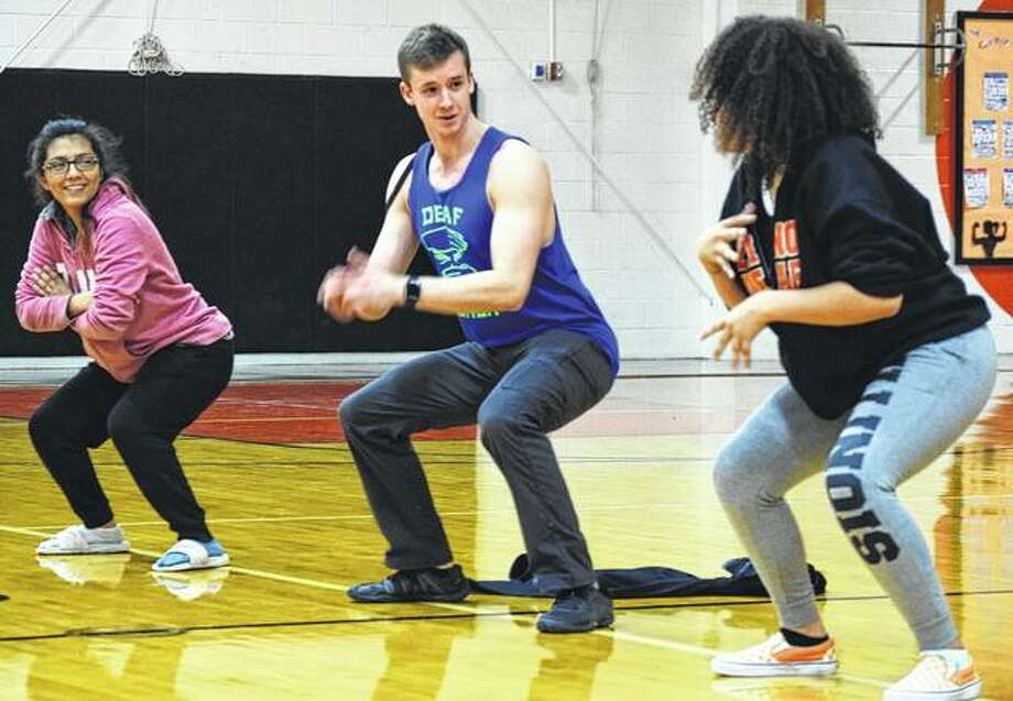 American Ninja Warrior competitor Kyle Schulze has a casual conversation with Estrella Gomez, 17, of Aurora and Kayla Ciganek-Harris, 17, of Chicago, while the three stay in a squat position for as long as they can as part of a challenge on Friday. Photo: Nick Draper   Journal-Courier