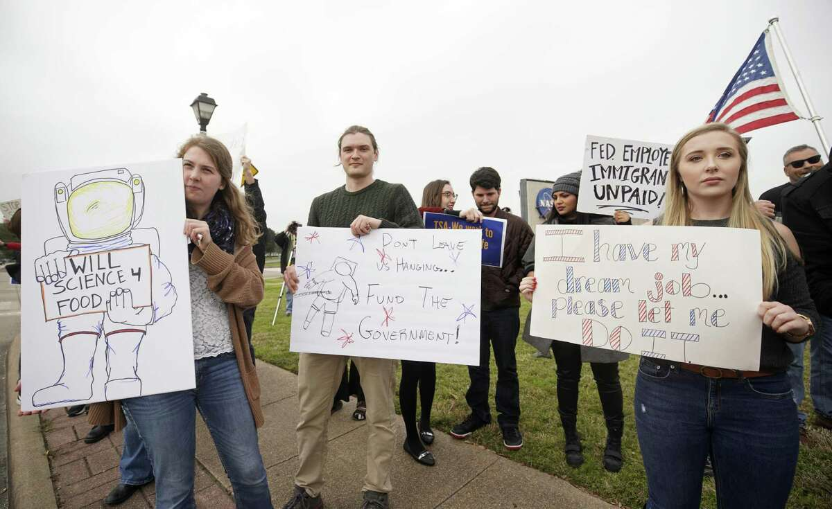 Kirsi Kuutti of Duluth, MN, left, Desmond O'Connor of Dickinson, center, and Sandra Jones, right, who was about to start a NASA job, protest with others outside of NASA's Johnson Space Center against the government shutdown Tuesday, Jan. 15, 2019, in Houston.