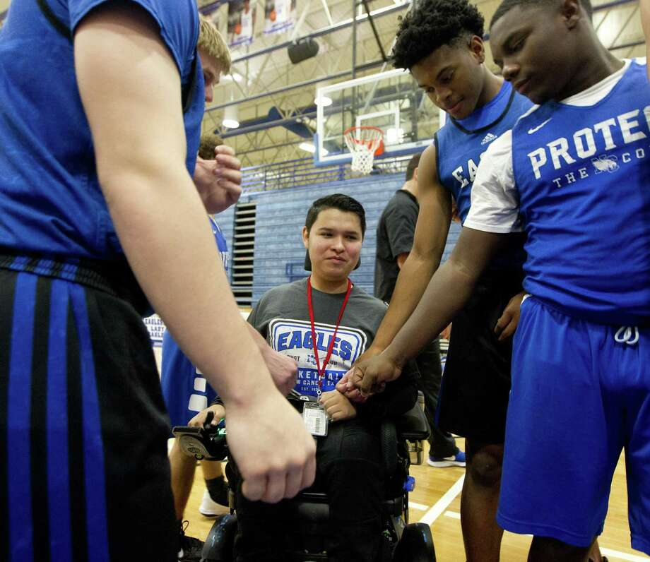 New Caney basketball manager Vincent Torres gets fist-bumps from teammates during basketball practice at New Caney High School, Wednesday, Jan. 16, 2019, in New Caney. Torres has muscular dystrophy, a disorder that affects the muscles used for moment, and joined the program as the team's manager this season after transfering from Atascocita High School. Photo: Jason Fochtman, Houston Chronicle / Staff Photographer / © 2019 Houston Chronicle
