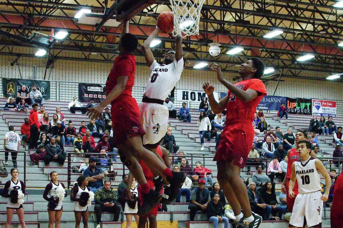 Pearland's Robert Charles (0) slips past Dawson's Jordan Marshall (14) for a basket Friday at Pearland High School.