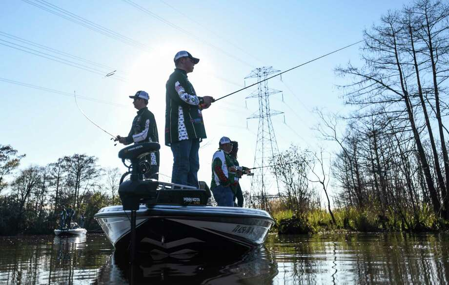 Little Cypress-Mauriceville's Payton LaFleur, 18, center, and Camden Morris, 16, left, practice fishing with their fishing team on the Sabine River in Orange Friday afternoon.