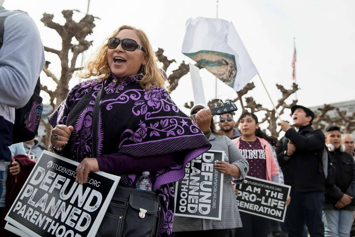 Maria Garcia of Salinas (left) sings while attending the annual anti-abortion Walk for Life event at Civic Center Plaza in San Francisco in January 2019. An October 2020 clash between anti-abortionists and counterprotesters in Walnut Creek recently resulted in criminal charges for two private security guards.