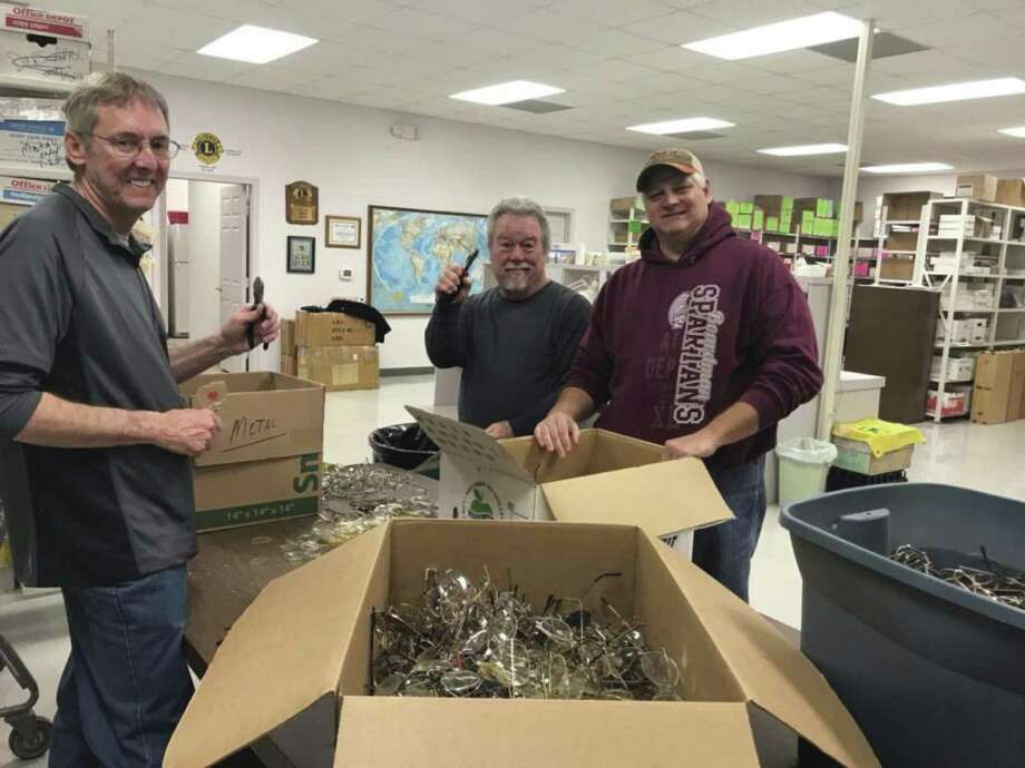Conroe Noon Lions Club VP Scott Perry, right, gives new membersGlenn Slater, left, and Craig Moore, center,instructions for popping lens on unusable eyeglasses to recycled for scrap metal.