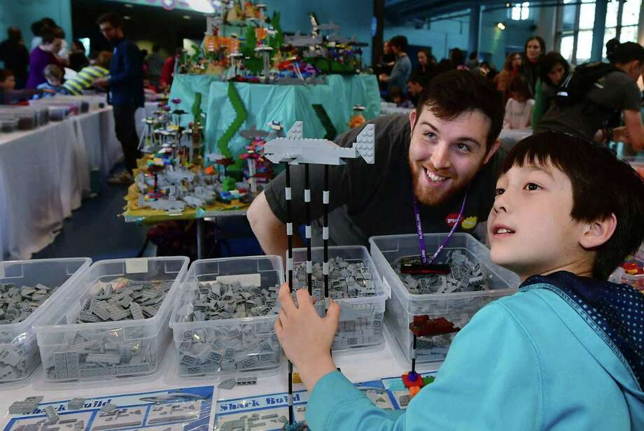 """Visitors to The Maritime Aquarium including Reima Waller, 7 from New Haven, helps Play-Well TEKnologies engineer Scott Delahunt create an enormous Aquarium-themed scene using Lego building blocks during """"LEGO Weekend"""" Saturday, January 26, 2019, at the aquarium in Norwalk, Conn. Throughout the weekend, The LEGO experts from Play-Well TEKnologies engineer a giant project made entirely out of LEGO blocks in Newman's Own Hall. Visitors build small LEGO marine creature from a diagram or create pieces of their choosing that will be part of the finished display. The event continues Sunday. Photo: Erik Trautmann / Hearst Connecticut Media / Norwalk Hour"""