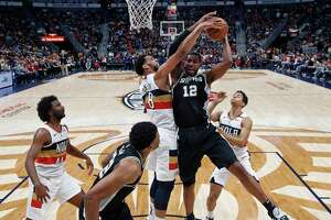 San Antonio Spurs center LaMarcus Aldridge (12) battles under the basket against New Orleans Pelicans center Jahlil Okafor (8) in the first half of an NBA basketball game in New Orleans, Saturday, Jan. 26, 2019. (AP Photo/Gerald Herbert)