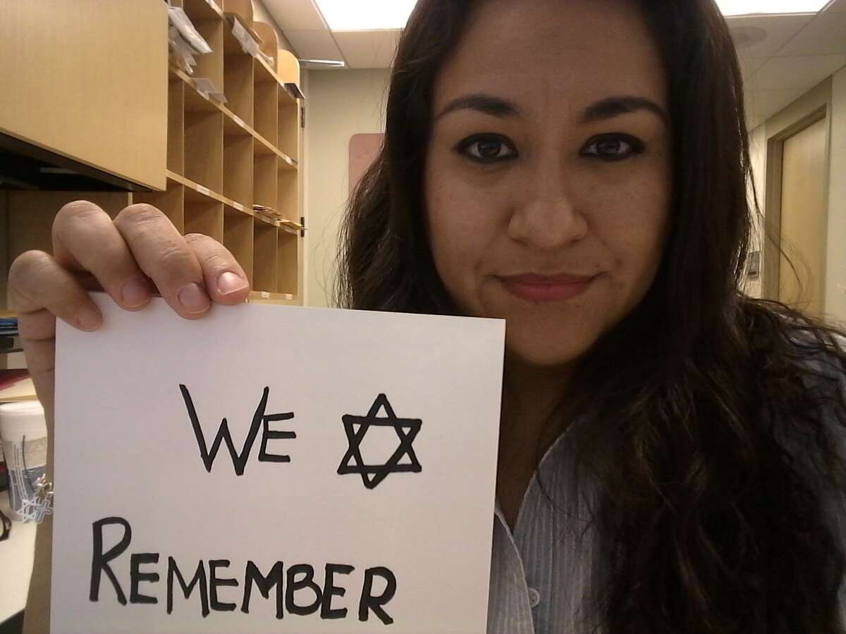 Barbara Gutierrez-Flores, from Houston, holds a sign reading #WeRemember with which she joined a social media campaign with the same hashtag commemorating the International Holocaust Remembrance Day 2018.